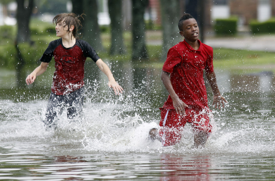 Photo - Conner Allen, 12, left, and Tyla Bradford, 11, right, play in a flooded street on Wednesday, April 27, 2011, in West Memphis, Ark. Strong storms hit the South for the second straight day Wednesday. (AP Photo/Mark Humphrey)