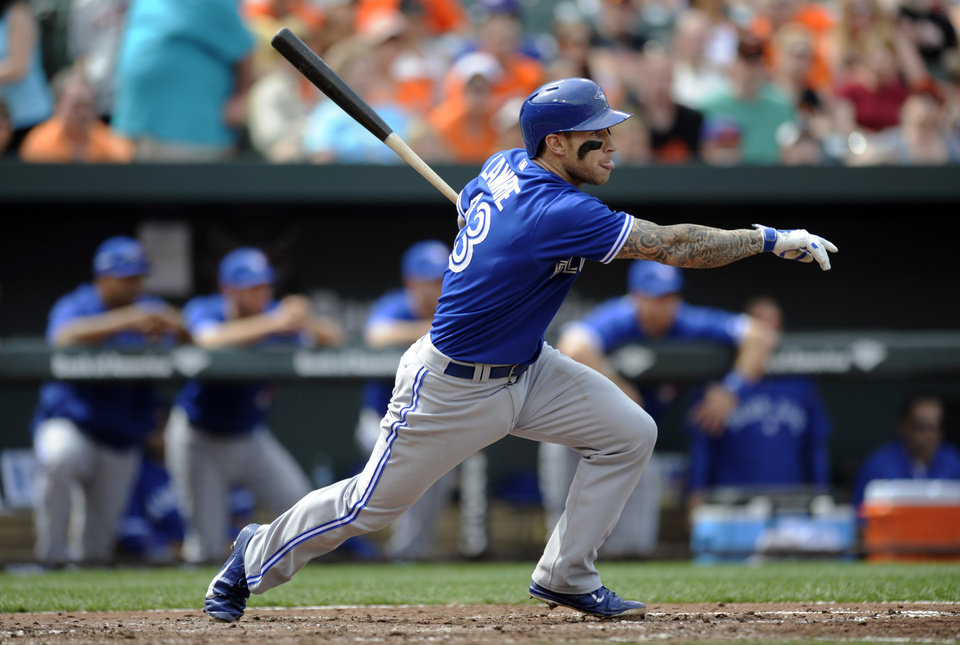 Photo - Toronto Blue Jays' Brett Lawrie follows through on a single against the Baltimore Orioles in the fourth inning of a baseball game on Sunday, April 13, 2014, in Baltimore. (AP Photo/Gail Burton)