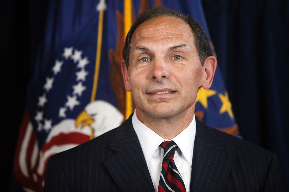 Photo - Former Procter and Gamble executive Robert McDonald, President Barack Obama's nominee as the next Veterans Affairs secretary, listens as Obama makes a statement at the Department of Veterans Affairs in Washington, Monday, June 30, 2014. If confirmed by the Senate, McDonald would succeed Eric Shinseki, the retired four-star general who resigned last month as the scope of the issues at veterans' hospitals became apparent. (AP Photo/Charles Dharapak)