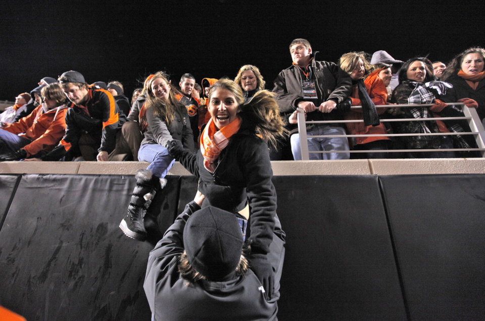 Photo - Cowboy fans leap off the wall to rush the field after OSU's 44-10 win over Oklahoma during the Bedlam college football game between the Oklahoma State University Cowboys (OSU) and the University of Oklahoma Sooners (OU) at Boone Pickens Stadium in Stillwater, Okla., Saturday, Dec. 3, 2011. Photo by Chris Landsberger, The Oklahoman
