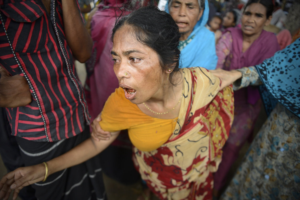Photo - A Bangladeshi woman mourns after the body of her daughter was retrieved from the rubble of the eight-story Rana Plaza building that collapsed in Savar, near Dhaka, Thursday, May 9, 2013. The death toll from the collapse of the garment factory building passed 900 on Thursday even as a fire in an 11-story garment factory Wednesday night in Dhaka killed eight people, including a ruling-party politician and a top official in the country's powerful clothing manufacturers' trade group. (AP Photo/Ismail Ferdous)