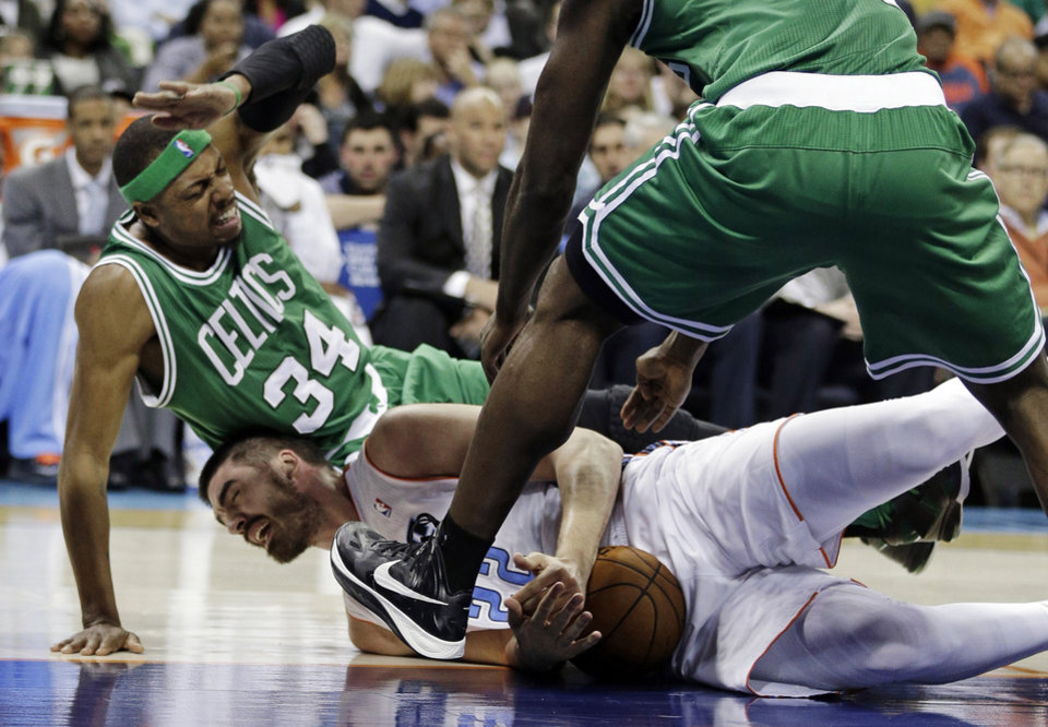 Photo - Charlotte Bobcats' Byron Mullens (22) holds onto the ball as Boston Celtics' Paul Pierce (34) falls on him during the first half of an NBA basketball game in Charlotte, N.C., Monday, Feb. 11, 2013. (AP Photo/Chuck Burton)