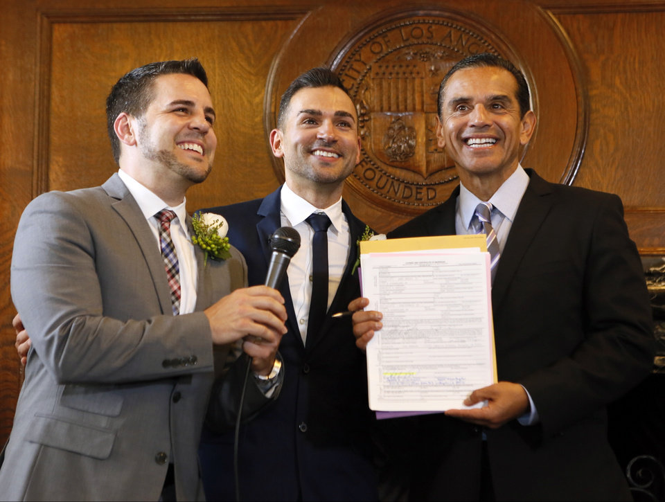 Photo - Jeff Zarrillo, left, and Paul Katami, center, pose for photos after being married by Los Angeles Mayor Antonio Villaraigosa, Friday June 28, 2013 at City Hall in Los Angeles. A three-judge panel of the 9th U.S. Circuit Court of Appeals issued a brief order Friday afternoon dissolving,