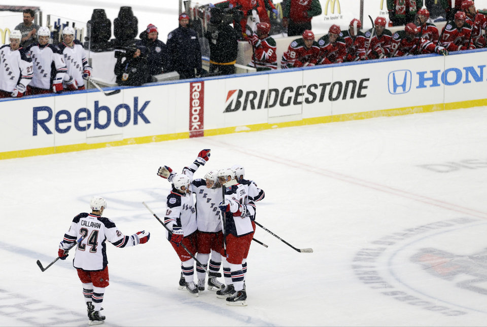 Photo - New York Rangers' Carl Hagelin, center, celebrates with teammates after scoring a goal during the second period of an outdoor NHL hockey game against the New Jersey Devils Sunday, Jan. 26, 2014, at Yankee Stadium in New York. (AP Photo/Frank Franklin II)