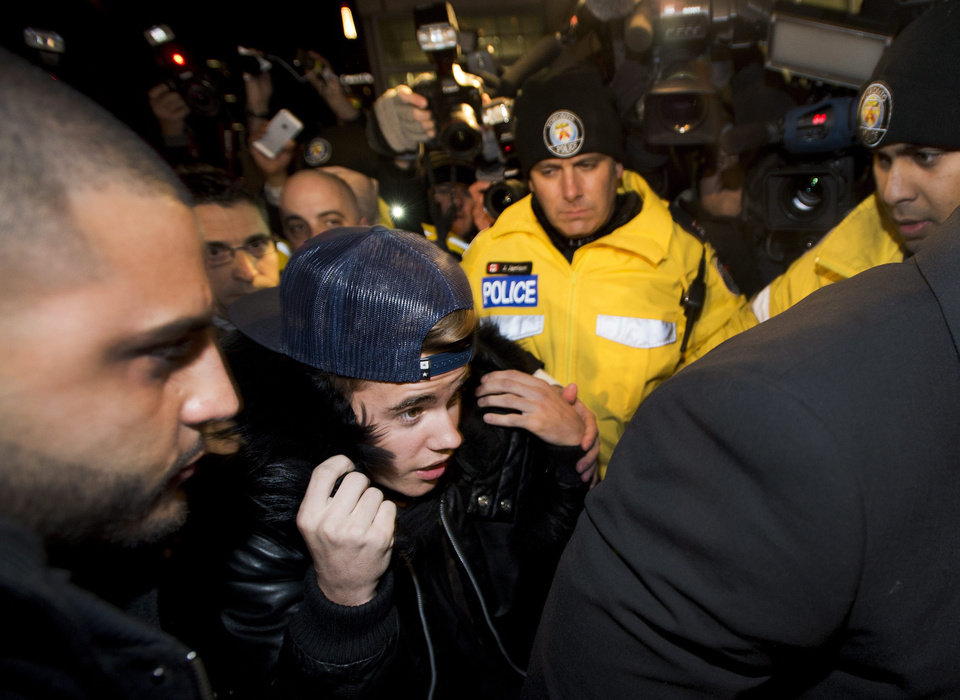 Photo - Canadian musician Justin Bieber is swarmed by media and police officers as he turns himself in to city police for an expected assault charge, in Toronto, on Wednesday, Jan. 29, 2014. A police official said the charge has to do with an alleged assault on a limo driver in December. (AP Photo/The Canadian Press, Nathan Denette)