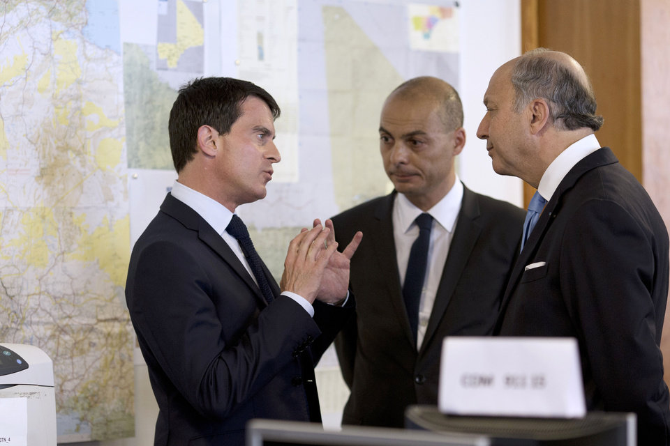 Photo - French Prime Minister Manuel Valls, left, speaks with French Foreign Affairs minister Laurent Fabius, right, and director of the French Foreign Affairs ministry's crisis center Didier Le Bret as they visit the French Foreign Affairs ministry's crisis center in Paris Friday, July 25, 2014, after a plane crashed in Mali. At least 116 people were killed in Thursday's disaster, nearly half of whom were French. One of two black boxes was recovered from the wreckage in the Gossi region of Mali near the border with Burkina Faso, and was taken to the northern city of Gao, where a French contingent is based. (AP Photo/Kenzo Tribouillard, Pool)