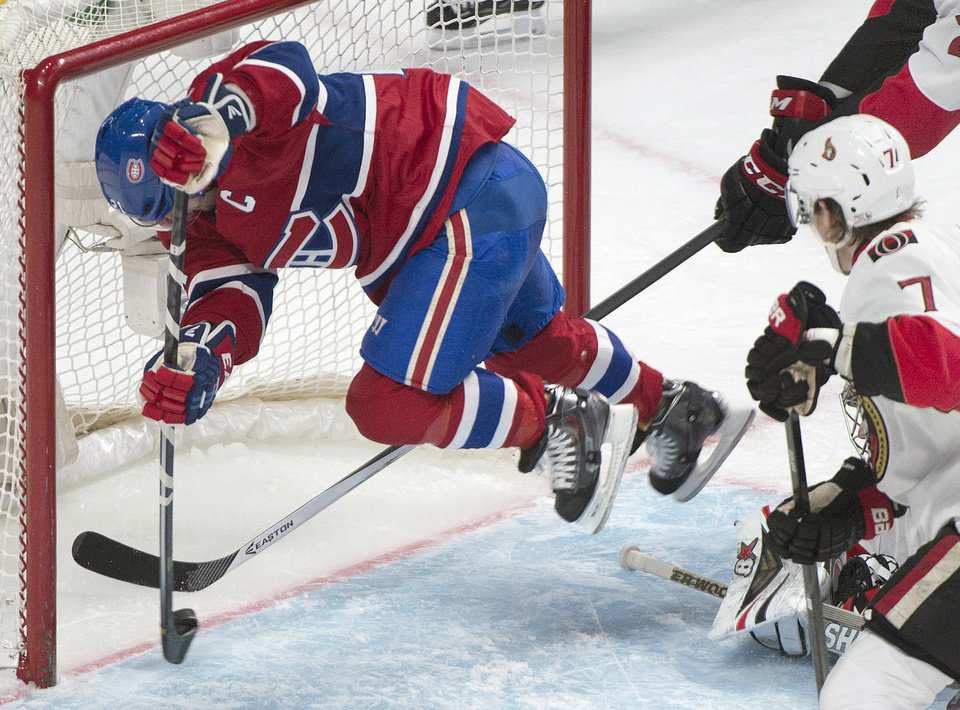 Photo - FILE - In this Jan. 4, 2014, file photo, Montreal Canadiens' Brian Gionta, left, scores against the Ottawa Senators as Senators Kyle Turris (7) is near during the third period of an NHL hockey game in Montreal. For the first time since 1973, there is just one Canadian team in the NHL postseason. The Canadiens represent the nation's only hope of ending a 21-year Stanley Cup drought. (AP Photo/The Canadian Press, Graham Hughes, File)