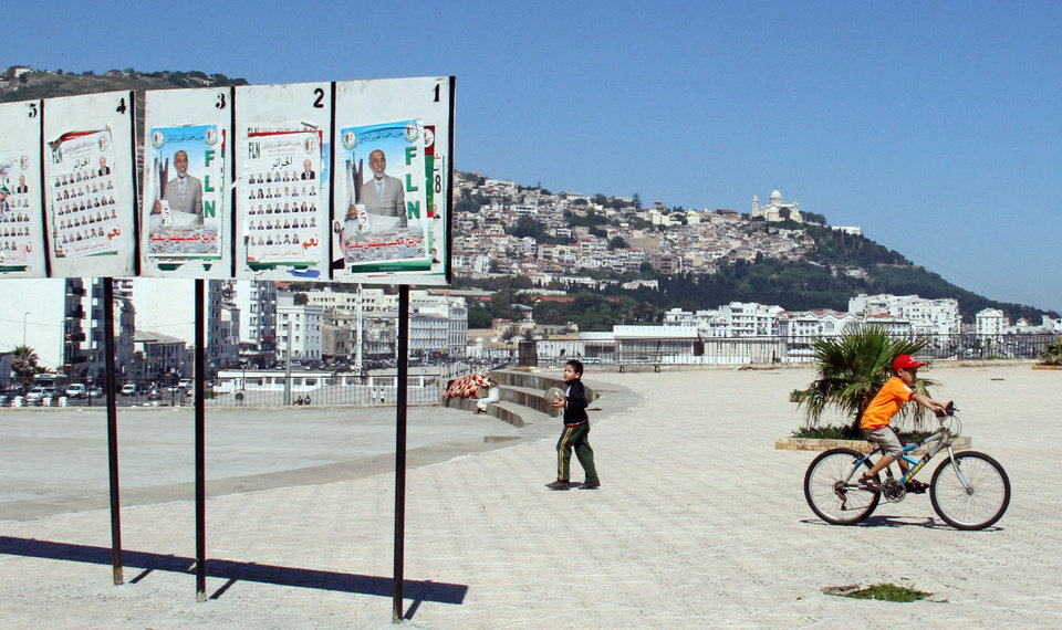 Photo -   Children play along the Algiers seaside by election posters and with the Notre Dame d'Afrique church in the distant background on Thursday May 10, 2012 while their schools are being used as voting stations. Parliamentary elections in Algeria are being billed as the fairest in 20 years, but as polls opened Thursday disgruntled Algerians appeared to be showing little interest and even outright scorn for the vote. (AP Photo/Paul Schemm).