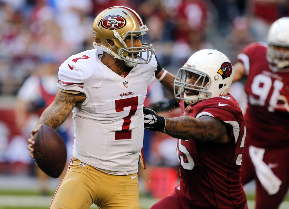 Photo - San Francisco 49ers quarterback Colin Kaepernick (7) is pressured by Arizona Cardinals outside linebacker John Abraham during the first half of an NFL football game, Sunday, Dec. 29, 2013, in Glendale, Ariz.  (AP Photo/Rick Scuteri)