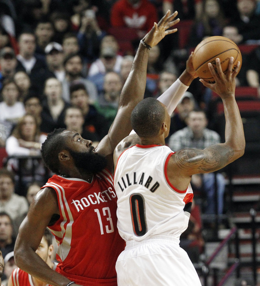 Houston Rockets guard James Harden, left, defends as Portland Trail Blazers guard Damian Lillard shoots during the first half of their NBA basketball game in Portland, Ore., Friday, Nov. 16, 2012. (AP Photo/Don Ryan)