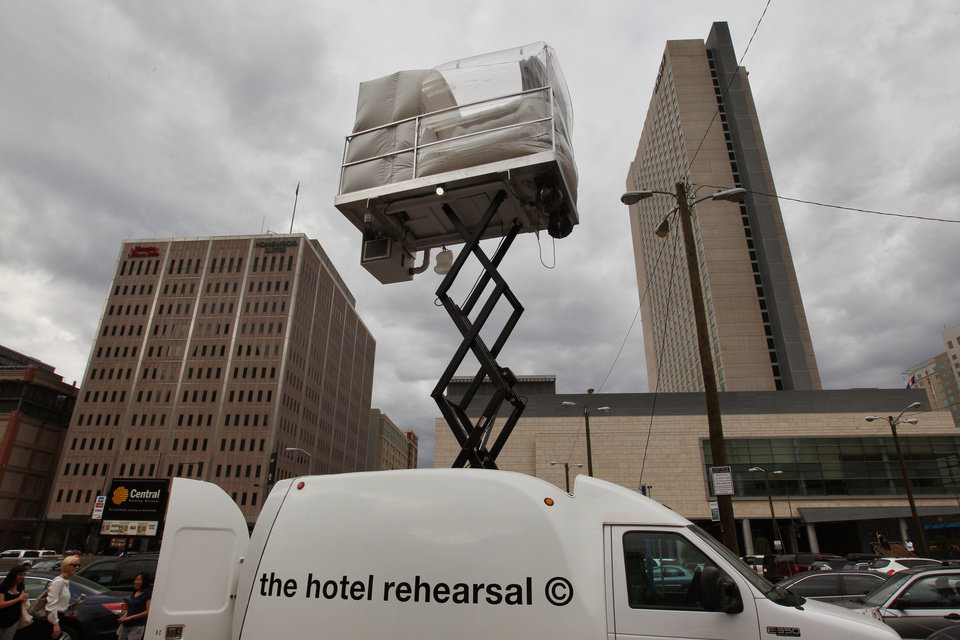 Photo - A hotel room made of aluminum and inflated vinyl is held aloft by a van-mounted scissor lift, on promotional display in a parking lot in downtown Denver, Wednesday July 25, 2013. Architectural artist Alex Schweder created the 5 by 7 foot room atop a van for the Biennial of the Americas in Denver. For $50,000, a guest would get one weekend night in the puffy space, plus lots of extras including a diamond pendant and earring set, two iPod Nanos and a dance party for 100 people in a ballroom of The Curtis Hotel. (AP Photo/Brennan Linsley)