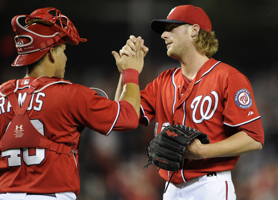 Photo - Washington Nationals relief pitcher Ross Detwiler, right, celebrates the team's 8-3 win over the Milwaukee Brewers with catcher Wilson Ramos, following a baseball game, Saturday, July 19, 2014, in Washington. (AP Photo/Nick Wass)