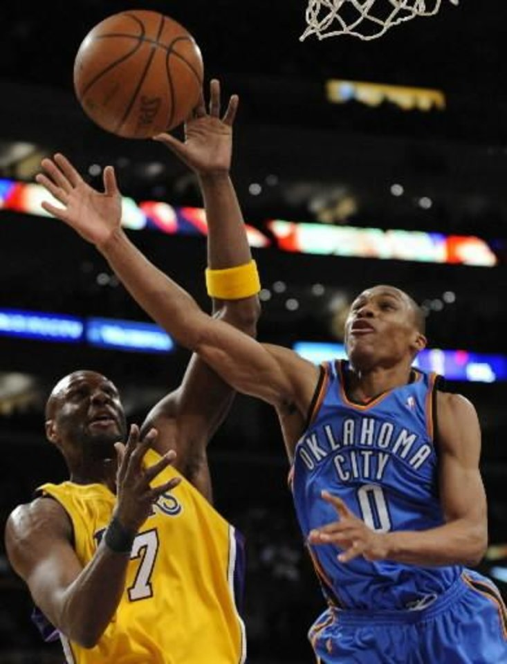 Photo - Los Angeles Lakers forward Lamar Odom (7) and Oklahoma City Thunder guard  Russell  Westbrook (0) fight for a rebound in the first half of an NBA basketball game, Tuesday, Feb. 10, 2009, in Los Angeles. Lakers won 105-98. (AP Photo/Gus Ruelas)