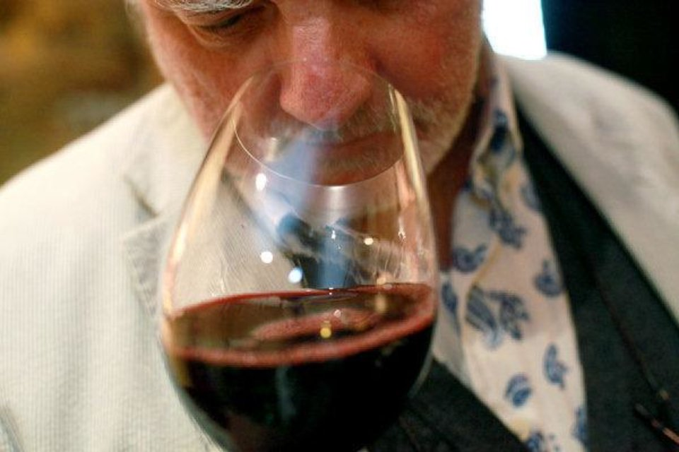 Photo - Philippe Garmy sniffs a glass of wine at the Atherton Hotel on the Oklahoma State University campus in Stillwater. The theme of this year's Wine Forum of Oklahoma is Beyond Borders. It will feature Chef Kurt Fleischfresser of Oklahoma City. Photo by John Clanton, The Oklahoman.  John Clanton