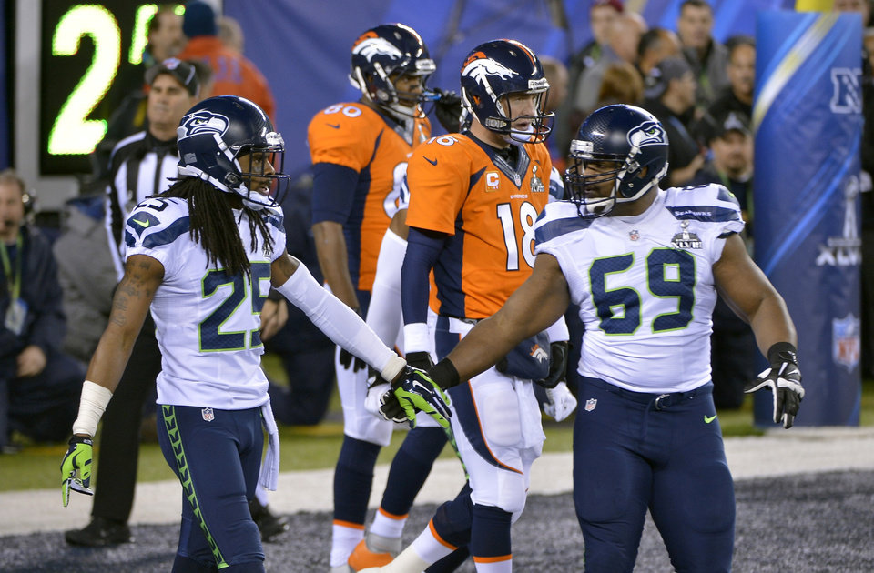 Photo - Seattle Seahawks' Richard Sherman, left, and Clinton McDonald, right, react in front of Denver Broncos' Peyton Manning (18) after a safety during the first half of the NFL Super Bowl XLVIII football game Sunday, Feb. 2, 2014, in East Rutherford, N.J. (AP Photo/Bill Kostroun)