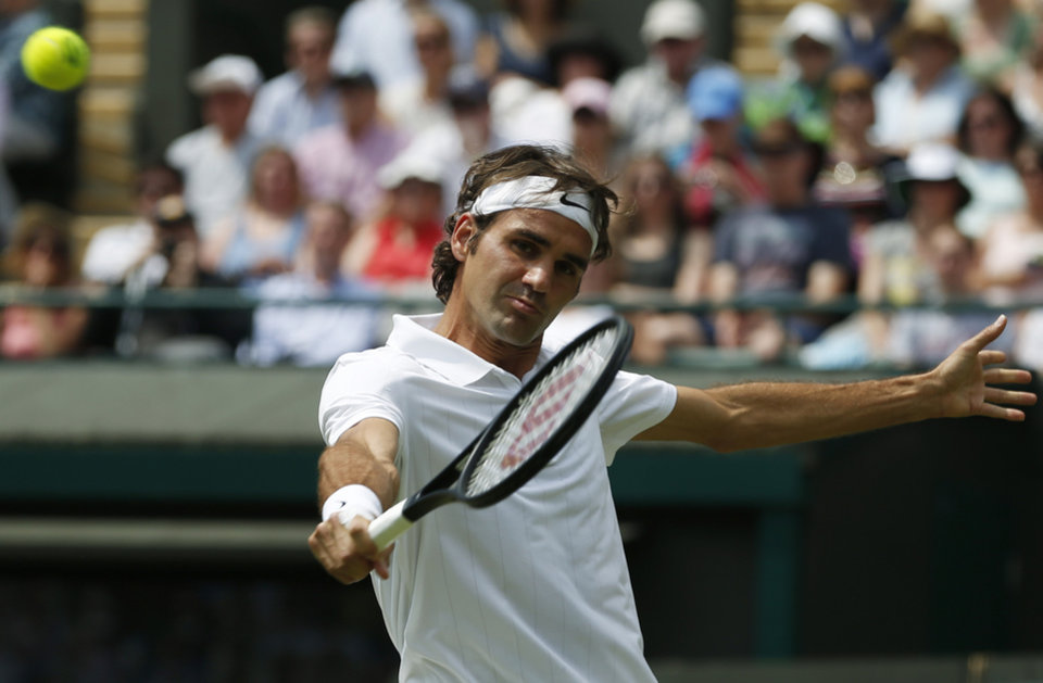 Photo - Roger Federer of Switzerland plays a return to Paolo Lorenzi of Italy during their first round match at the All England Lawn Tennis Championships in Wimbledon, London,  Tuesday, June  24, 2014. (AP Photo/Pavel Golovkin)