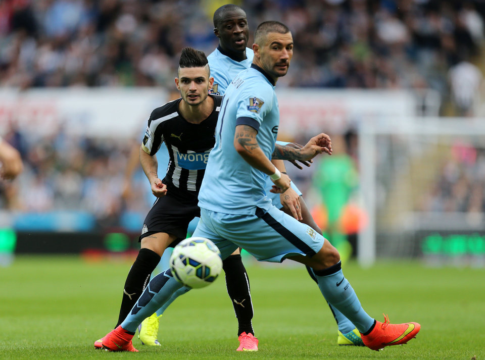 Photo - Newcastle United's Remy Cabella, left, vies for the ball with Manchester City's Aleksandar Kolarov, front, and Yaya Toure, back, during their English Premier League soccer match at St James' Park, Newcastle, England, Sunday, Aug. 17, 2014. (AP Photo/Scott Heppell)