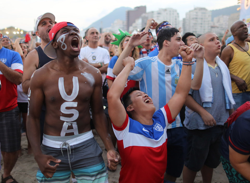 Photo - U.S. soccer fans watch their team's World Cup round of 16 match against Belgium on a live telecast inside the FIFA Fan Fest area on Copacabana beach in Rio de Janeiro, Brazil, Tuesday, July 1, 2014. (AP Photo/Leo Correa)