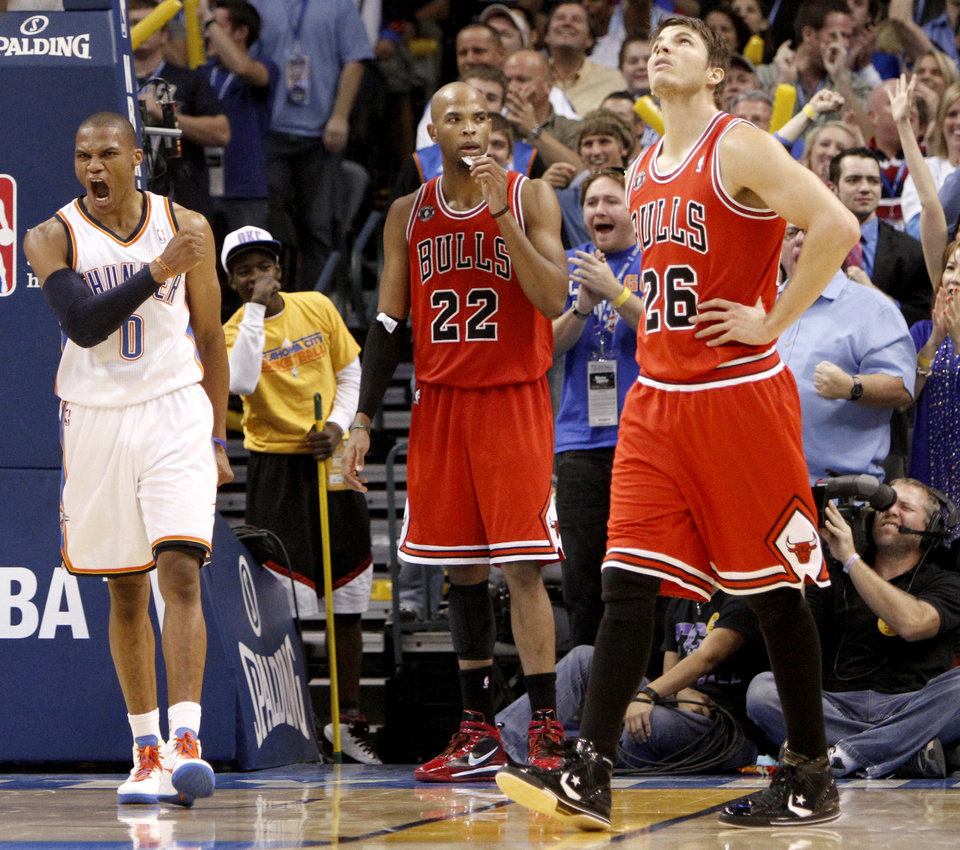Photo - Oklahoma City's Russell Westbrook celebrates after a dunk beside Chicago's Taj Gibson, center, and Kyle Korver during the NBA basketball game between the Oklahoma City Thunder and the Chicago Bulls in the Oklahoma City Arena on Wednesday, Oct. 27, 2010. Photo by Bryan Terry, The Oklahoman