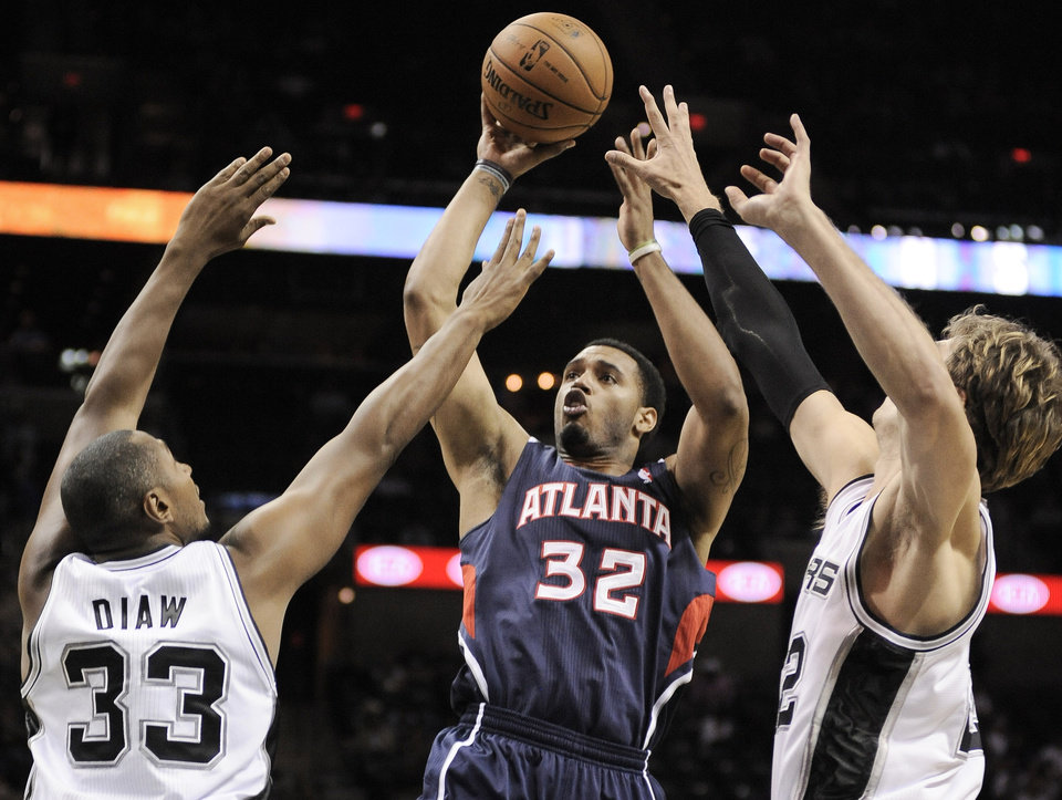 Atlanta Hawks' Mike Scott (32) shoots over San Antonio Spurs' Boris Diaw (33), of France, and Tiago Splitter, of Brazil, during the second half of an NBA preseason basketball game, Wednesday, Oct. 10, 2012, in San Antonio. San Antonio won 101-99. (AP Photo/Darren Abate)