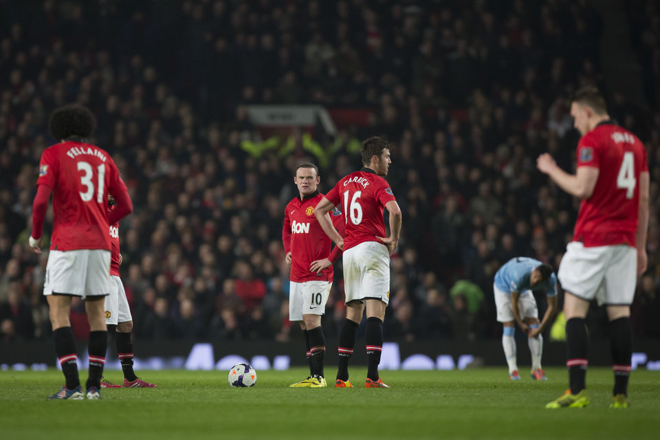Photo - Manchester United's Wayne Rooney, center, and Michael Carrick, center right, wait with teammates for play to begin after a second goal by Manchester City's Edin Dzeko, out of frame, during their English Premier League soccer match at Old Trafford Stadium, Manchester, England, Tuesday March 25, 2014. (AP Photo/Jon Super)