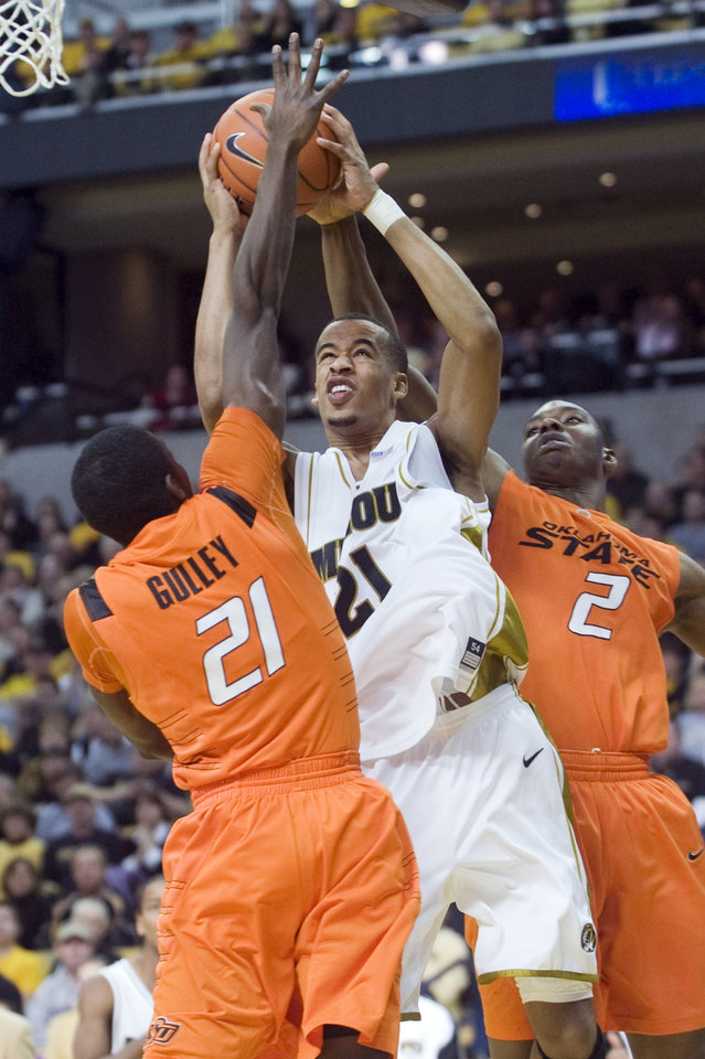 Photo - OSU: Missouri's Laurence Bowers, center, shoots the ball between Oklahoma State University's Fred Gulley, left, and Oklahoma State's Obi Muonelo, right, during the second half of their NCAA college basketball game Saturday, Jan. 30, 2010, in Columbia, Mo. Missouri won the game 95-80. (AP photo/L.G. Patterson) ORG XMIT: MOLG105