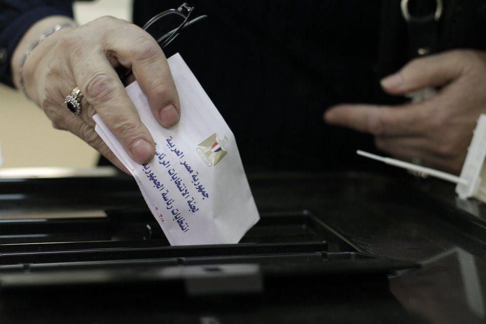 Photo -   An Egyptian woman casts her ballot in the country's presidential election on Wednesday, May 23, 2012 in the Zamalek neighborhood of Cairo, Egypt. The ballot, in Arabic, reads,