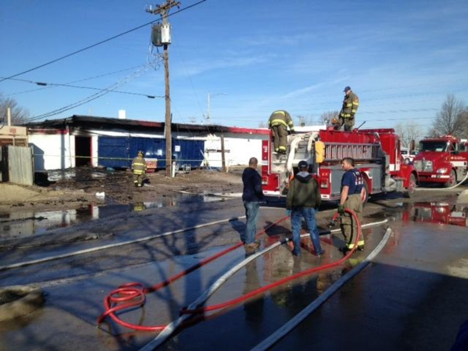 Fire crews roll up hoses after a fire in a Tuttle grocery store. Photo by Steve Sisney