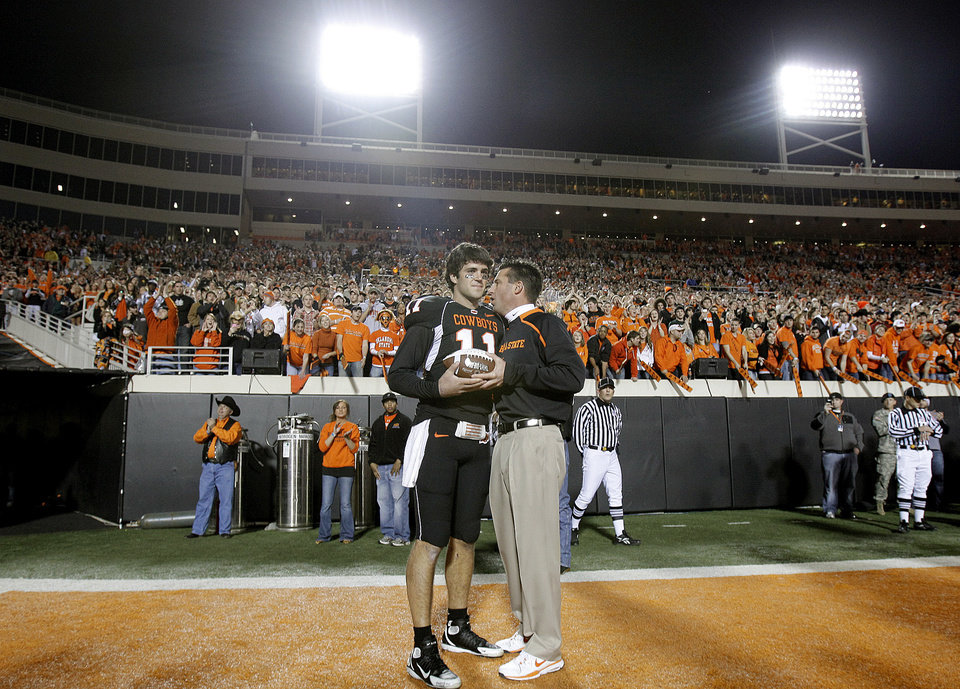 Photo - OSU head coach Mike Gundy greets quarterback Zac Robinson (11) as 