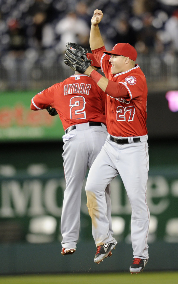 Photo - Los Angeles Angels center fielder Mike Trout (27) celebrates with teammate Erick Aybar (2) after a 4-2 win over the Washington Nationals with Erick Aybar (2) in a baseball game, Monday, April 21, 2014, in Washington. (AP Photo/Nick Wass)
