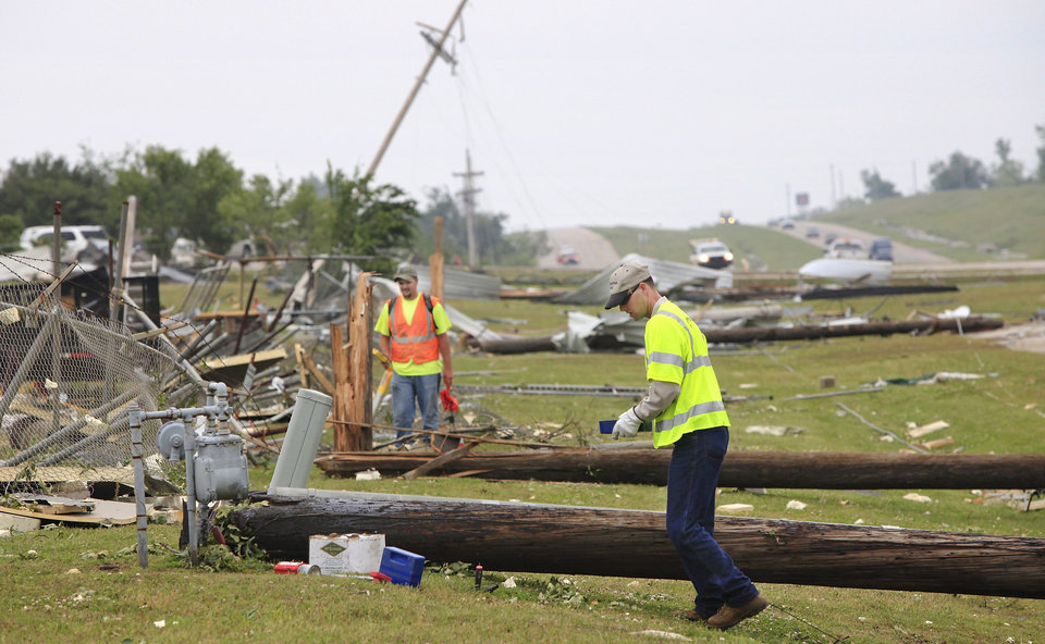 Photo - Workers for utility companies use devices  to check damage to gas meters and electrical lines in an area along State Highway 99 that received heavy damage in tornado that hit the community, located about 50 miles east of Oklahoma City,  Monday night.  Photo by Jim Beckel, The Oklahoman