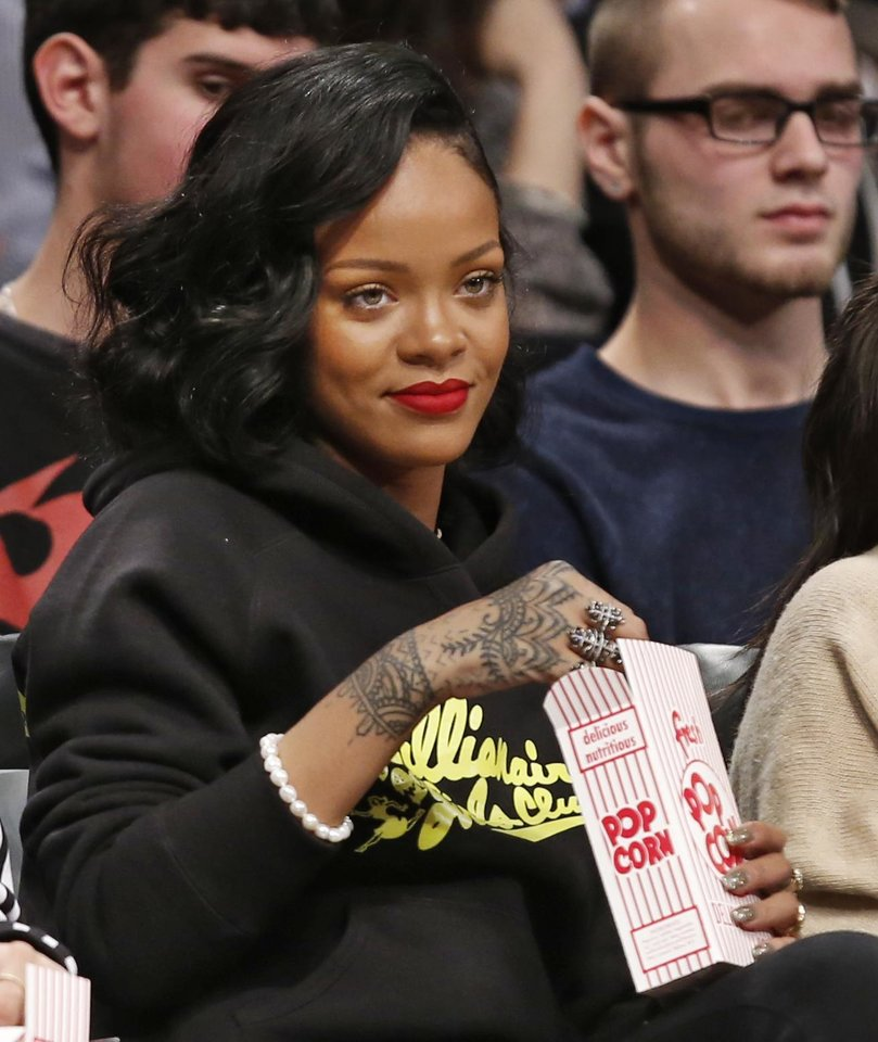 Photo - Singer Rihanna watches the Atlanta Hawks face the Brooklyn Nets in an NBA basketball game at the Barclays Center, Monday, Jan. 6, 2014, in New York. (AP Photo/Kathy Willens)
