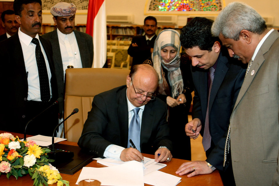 Photo - In this photo provided by Yemen's Defense Ministry, Yemeni President Abed Rabbo Mansour Hadi signs the final approval on transforming Yemen into a federal state of six regions in Sanaa Yemen, Monday, Feb. 10, 2014. A key Yemeni panel tasked with devising a new system to address the local grievances that have fed the impoverished Arabian Peninsula nation's instability agreed Monday to transform the country into a state of six regions. (AP Photo/Yemen's Defense Ministry)