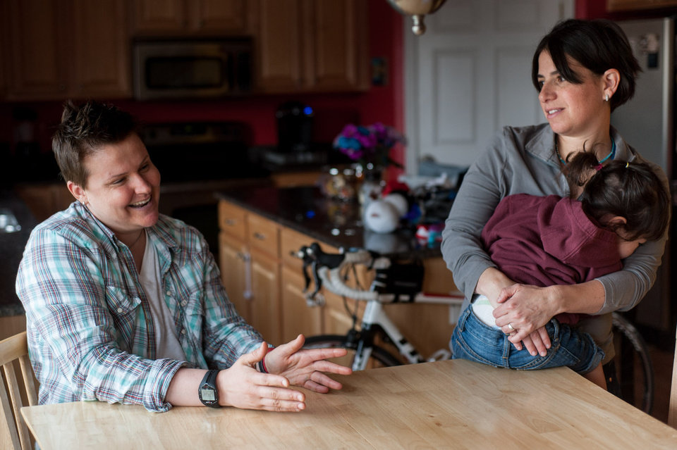Photo - FILE - In this May 17, 2013, photo, Niki Quasney, left, talks about her ongoing battle with ovarian cancer as her partner, Amy Sandler, and daughter stand nearby at their home in Munster, Ind. Quasney receives treatment at hospitals in neighboring Illinois because she and Sandler, who wed last year in Massachusetts, fear that a private hospital near their Indiana home might not allow them to be together should Quasney suffer a medical emergency because of the state's marriage ban. (AP Photo/The Times, Kyle Telechan, File)