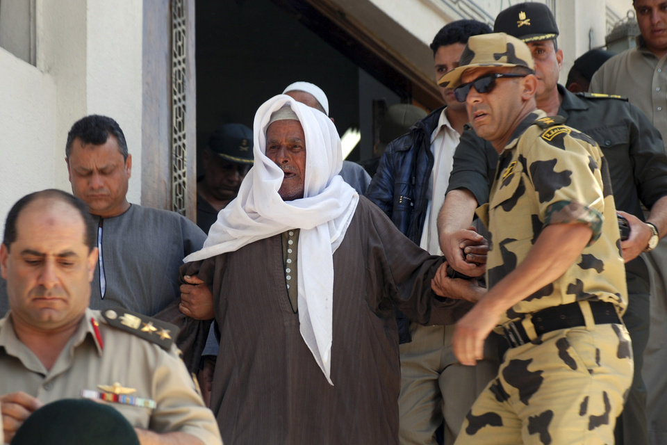 Photo -   A relative of Egyptian commando Cpl. Samir Anwar Ismail, who was killed in clashes with protesters, is assisted during the funeral in Cairo, Egypt, Saturday, May 5, 2012. Lawyers say authorities have detained over 300 Egyptian protesters including 18 women following clashes outside the country's Defense Ministry, accused of attacking troops and disrupting public order.(AP Photo)