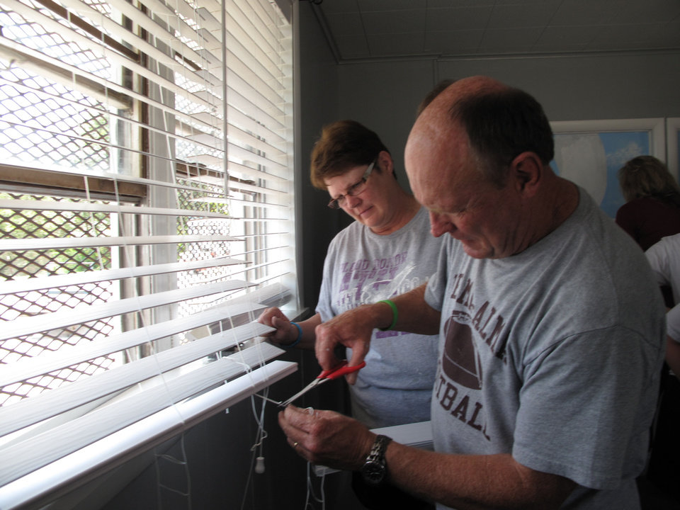 Photo - Sherrie and Randy Smith of Velma hang new blinds on a window in the Jesus House prayer room during a refurbishment project in honor of Braylee Rae Henry, 16.  CARLA HINTON - CARLA HINTON