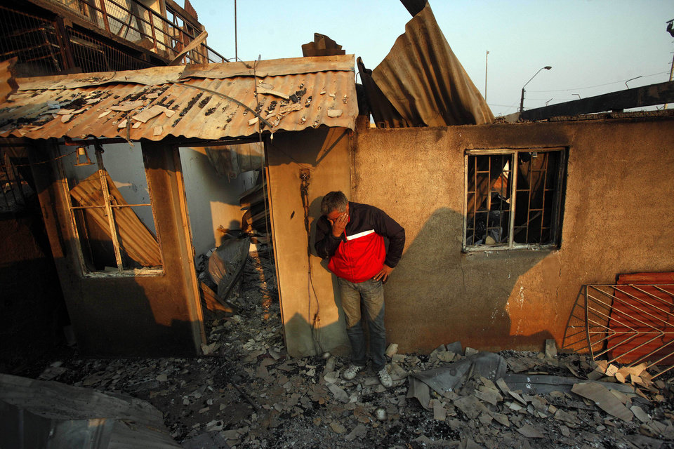 Photo - A man cries next to the remains of his house after a forest fire destroyed it in Valparaiso, Sunday, April 13, 2014. A raging fire leaped from hilltop to hilltop in this port city, killing at least 16 people and destroying more than 500 homes. More than 10,000 people were evacuated. (AP Photo/ Luis Hidalgo)