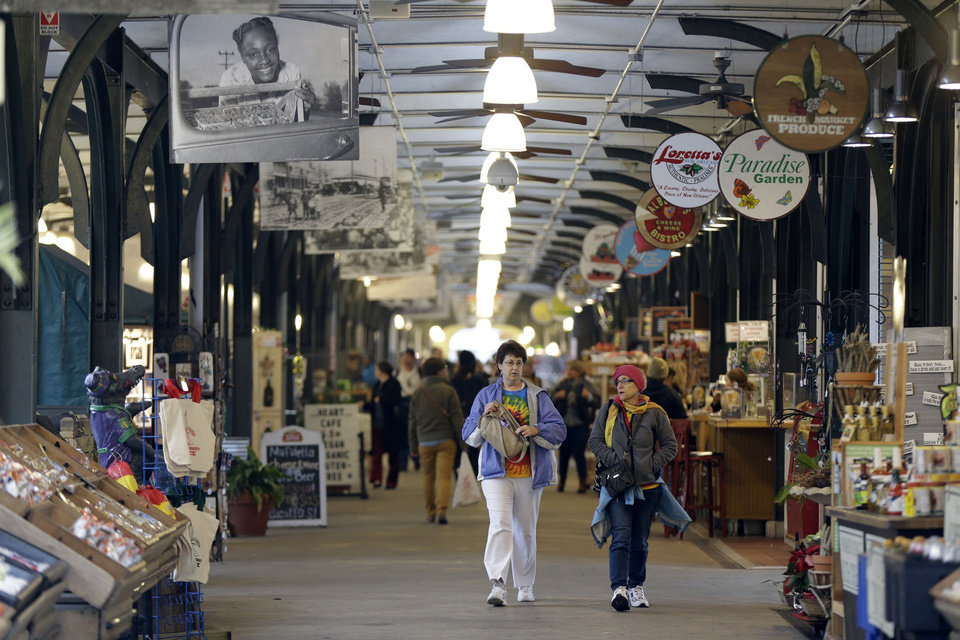 Photo - This Jan. 15, 2013 photo shows people walking through the French Market in New Orleans. The centuries-old commercial hub stretches for several city blocks along the bank of the Mississippi River in the French Quarter and includes Cafe du Monde, home of the deep-fried, sugar-coated beignet, a popular New Orleans pastry. (AP Photo/Gerald Herbert)