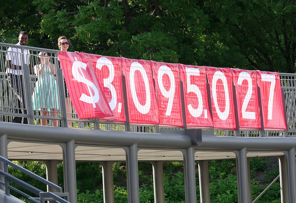 Photo - Volunteers at the 2012 Allied Arts Campaign Celebration at the Myriad Botanical Gardens on Tuesday unveil a banner with the total for this year's campaign donations, a record for the annual fundraiser. Photos by David Faytinger, for the Oklahoman