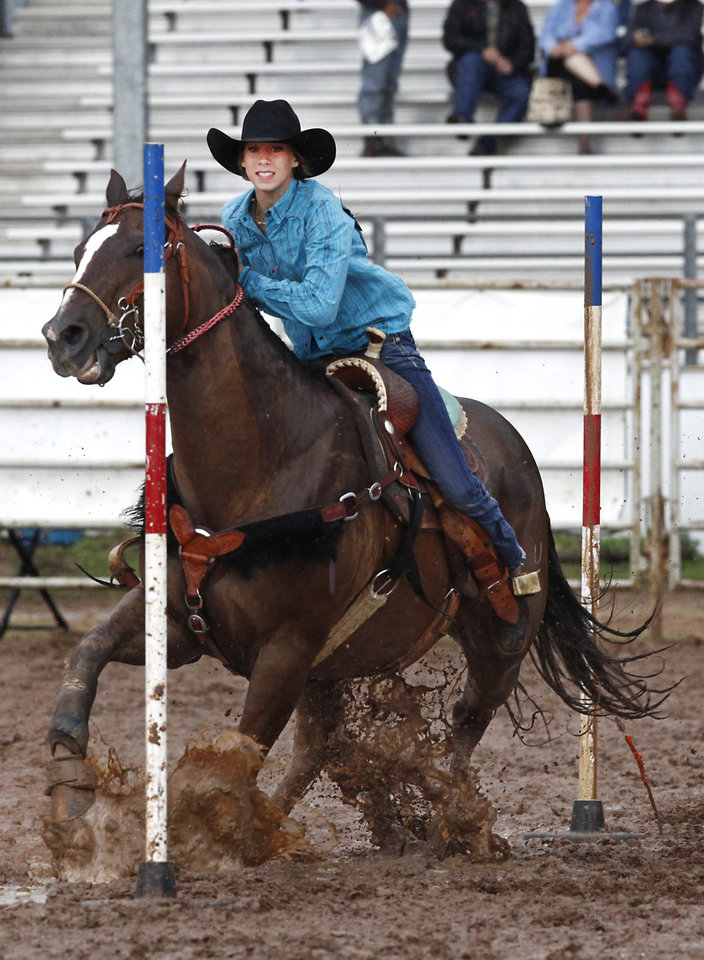 Photo - Reece Buckmaster, Weatherford, OK, competes in a muddy Pole Bending at the International Youth Finals Rodeo in Shawnee at the Heart of Oklahoma Exposition Center, Wednesday, July 9, 2014. Photo by David McDaniel, The Oklahoman