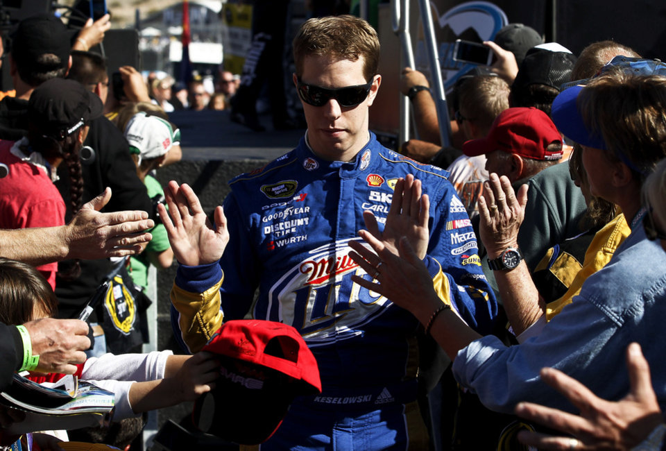 Brad Keselowski high-fives fans prior to a NASCAR Sprint Cup Series auto race at Phoenix International Raceway, Sunday, Nov. 11, 2012, in Avondale, Ariz. (AP Photo/Ross D. Franklin)