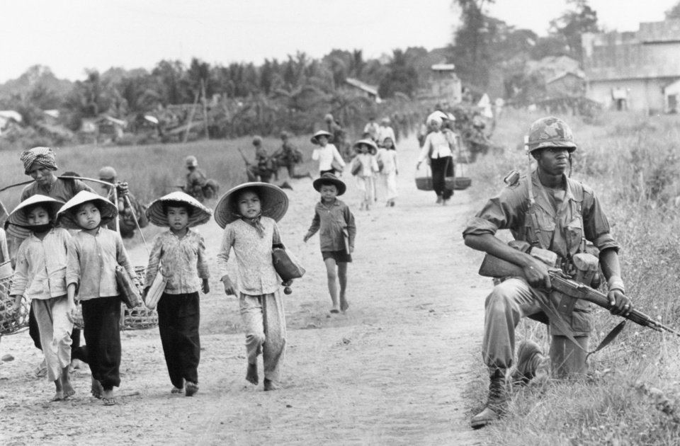 Photo -   File - In this December 1965 file photo shot by Associated Press photographer Horst Faas, a U.S. 1st Division soldier guards Route 7 as Vietnamese women and school children return home to the village of Xuan Dien from Ben Cat, Vietnam. Faas, a prize-winning combat photographer who carved out new standards for covering war with a camera and became one of the world's legendary photojournalists in nearly half a century with The Associated Press, died Thursday May 10, 2012. He was 79. (AP Photo/Horst Faas)