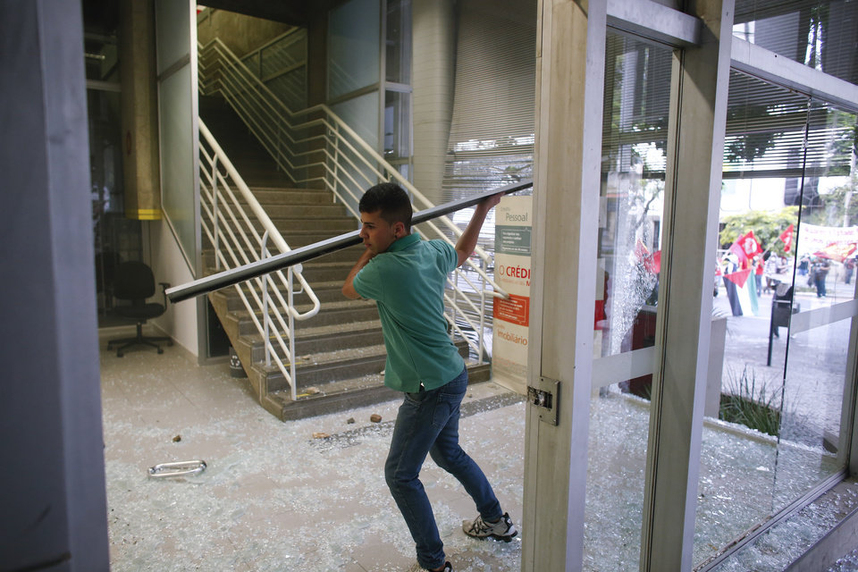 Photo - A protester brakes the window of a bank  during a demonstration against the 2014 World Cup in Belo Horizonte, Brazil, Thursday, June, 12, 2014. Demonstrators gathered in downtown Belo Horizonte to protest against the 2014 World Cup soccer tournament. (AP Photo/Victor R. Caivano)