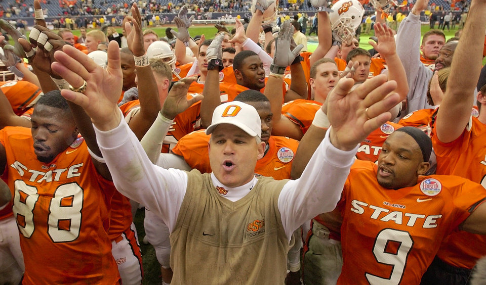 Photo - Oklahoma State vs. Southern Mississippi college football in the Houston Bowl at Reliant Stadium in Houston, Texas, Friday, December 27, 2002. OSU head coach Les Miles and his players sing the alma mater to Cowboys fans after their 33-23 win over Southern Mississippi in the Houston Bowl. Next to Miles are Willie Young, left, and Darrent Williams, right. Staff photo by Nate Billings.