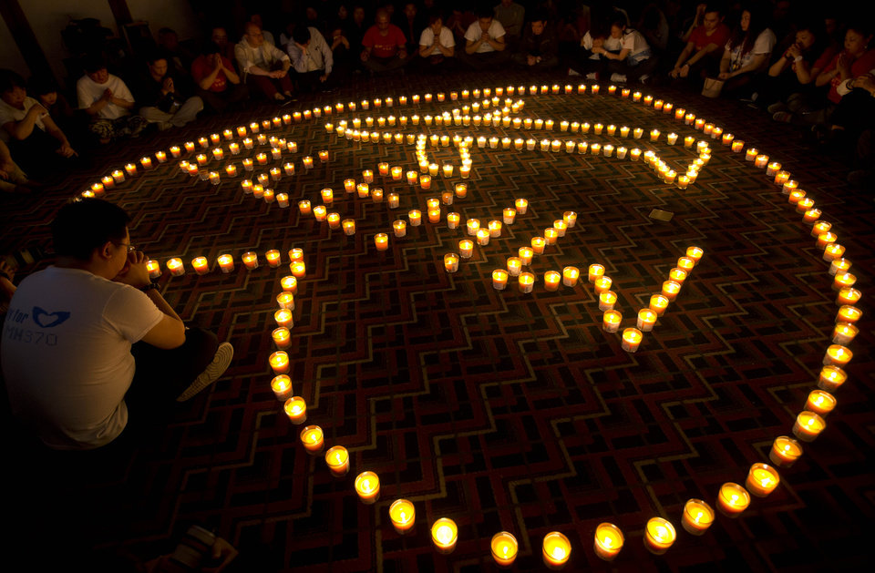 Photo - FILE - In this April 8, 2014 file photo, relatives of Chinese passengers onboard Malaysia Airlines Flight 370 offer prayers during a candlelight vigil for their loved ones at a hotel in Beijing, China. The Malaysian government on Tuesday, May 27, 2014, released 47 pages of raw satellite data used to conclude that the missing Malaysia Airlines jet crashed into the southern Indian Ocean. Some family members of the 239 people on board have been demanding Malaysia release the data so that independent experts can verify it. (AP Photo/Andy Wong, File)