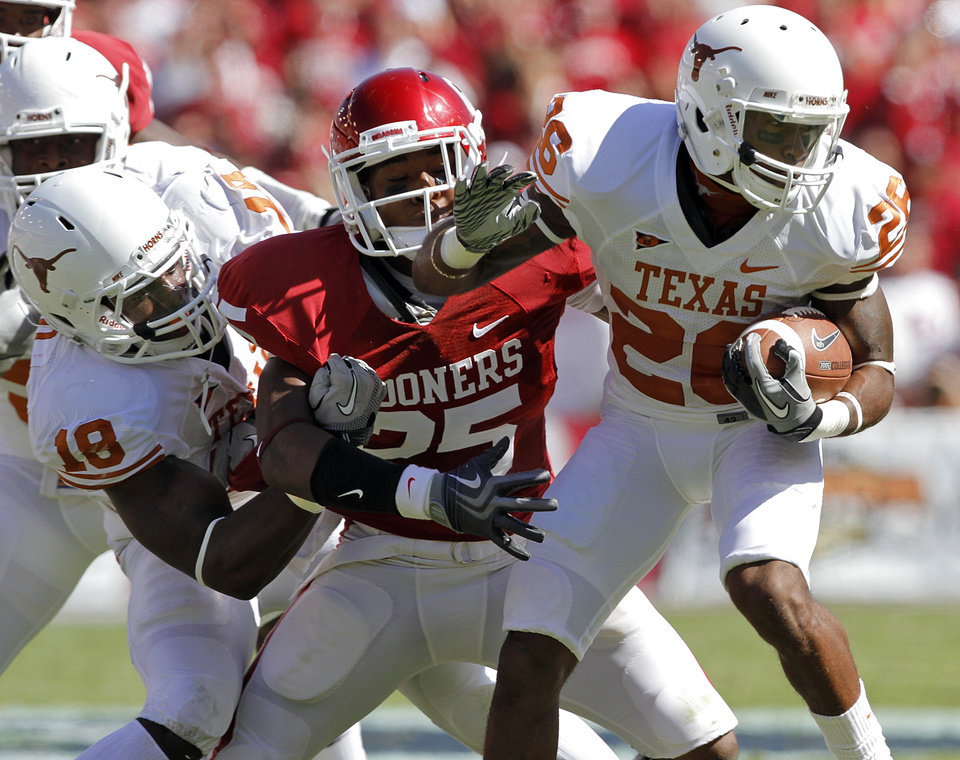 Photo - Texas' Emmanuel Acho (18) tries to keep Oklahoma's Corey Nelson (25) from stopping Longhorn D.J. Monroe (26) in the first half of the Red River Rivalry college football game between the University of Oklahoma Sooners (OU) and the University of Texas Longhorns (UT) at the Cotton Bowl on Saturday, Oct. 2, 2010, in Dallas, Texas.   Photo by Chris Landsberger, The Oklahoman