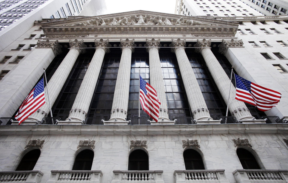 Photo - FILE - In this Feb. 10, 2011 file photo, American flags fly in front of the New York Stock Exchange, in New York. Asian stock markets were mostly higher Tuesday, Aug. 12, 2014, as tensions over Ukraine and Iraq eased, giving investors the confidence to dip into riskier assets. European shares drifted. (AP Photo/Mark Lennihan, File)