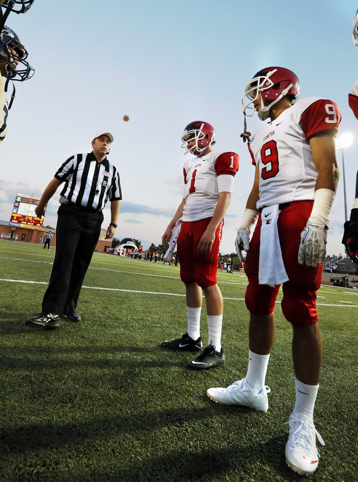 Photo - Lawton's Dallas Sealey (1) and Bryce Birt (9) watch the coin toss as the Southmoore Sabercats play the Lawton High School Wolverines in high school football on Friday, Oct. 11, 2013, in Moore, Okla. Photo by Steve Sisney, The Oklahoman