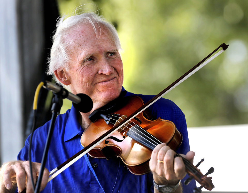 Photo - Guthrie resident Byron Berline smiles at fellow musicians while playing his fiddle with Bobby Clark and other musicians on stage  at the 17th annual Oklahoma  International Bluegrass Festival in Cottonwood Flats Municipal Park in Guthrie.   The event, which features bluegrass bands and musicians from around the world, continues  through Saturday.  Photo  by Jim Beckel, The Oklahoman.  Jim Beckel - THE OKLAHOMAN