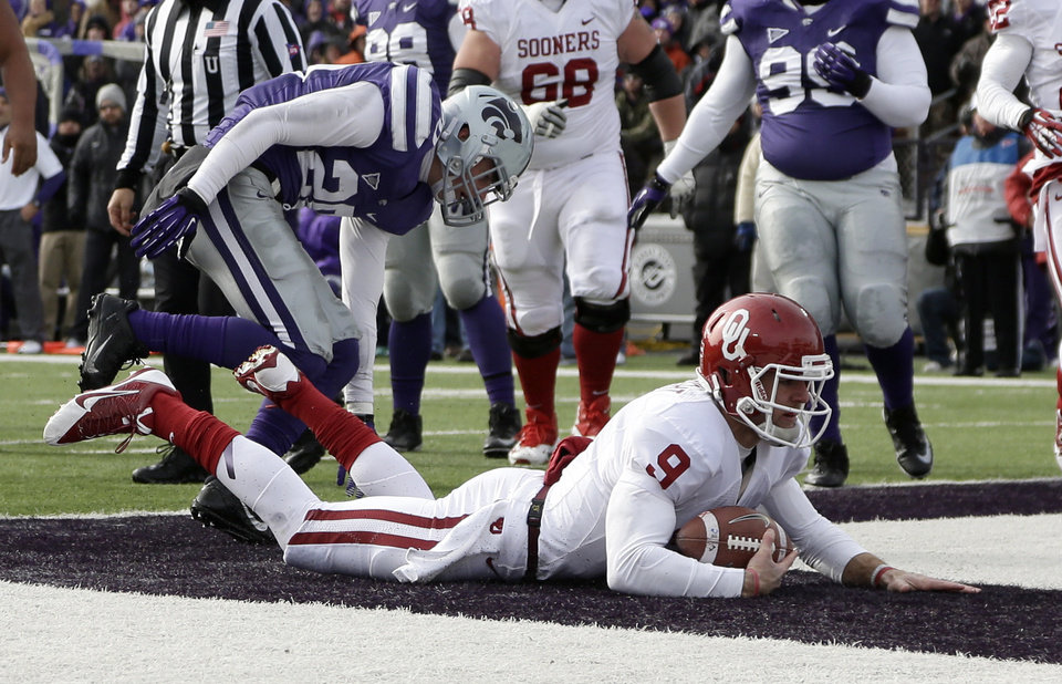 Oklahoma quarterback Trevor Knight (9) gets past Kansas State defensive back Dylan Schellenberg (20) to score a touchdown during the first half of an NCAA college football game Saturday, Nov. 23, 2013 in Manhattan, Kan. (AP Photo/Charlie Riedel)